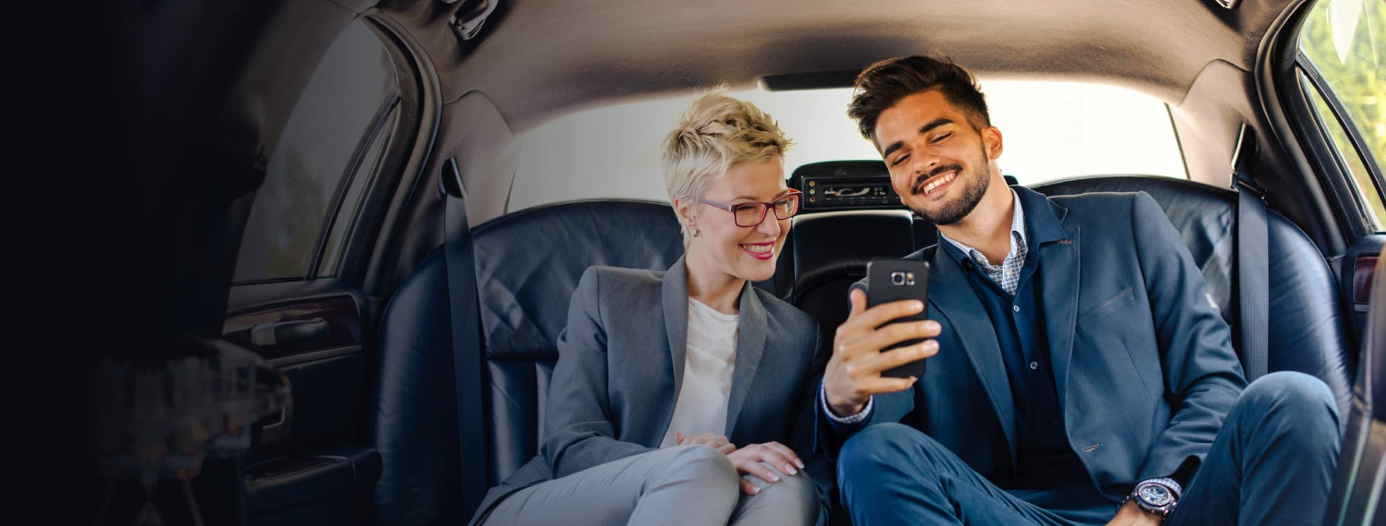 man and a woman inside a car looking at a smartphone