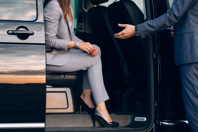 man in a suit helping a woman exit a van